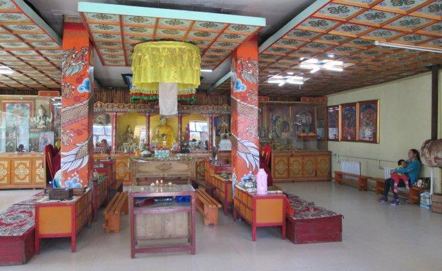 Вдали, в середине молитвенного зала находится большая статуя Будды