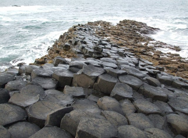 Каменный холм спускается к океану и продолжается под водой