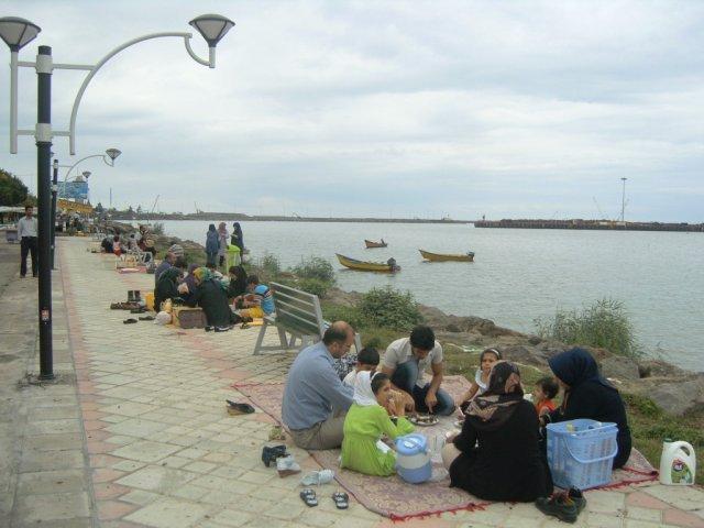 Иранцы отдыхают и обедают, сидя на коврах