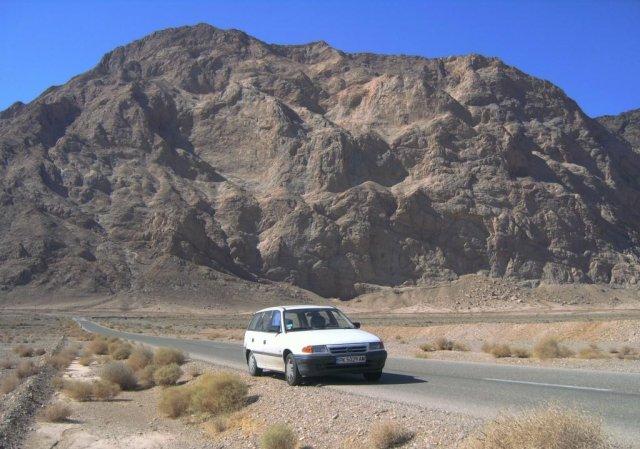 Моя машина на дорогах через пустынные районы с голыми скалами