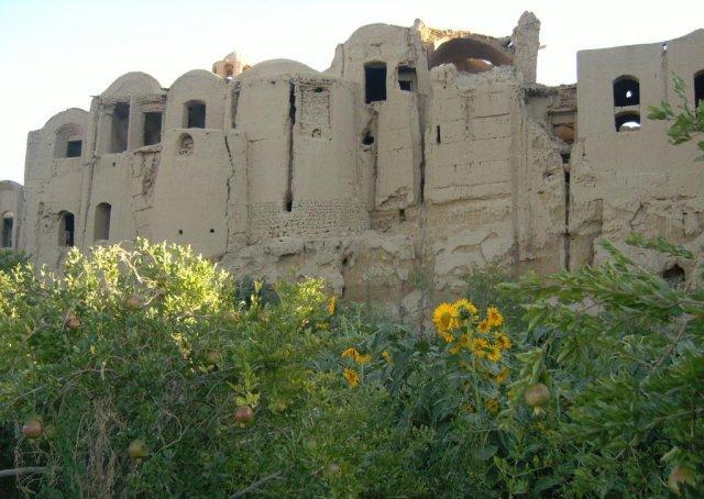 Крайние здания похожи на полуразрушенный замок из глины