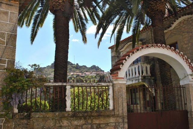 Вид на Монсанту из посёлка Релва через дворик с пальмами при особнячке.