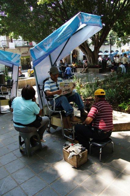 Чистильщик обуви на площади Сокало в Оахаке, Мексика
