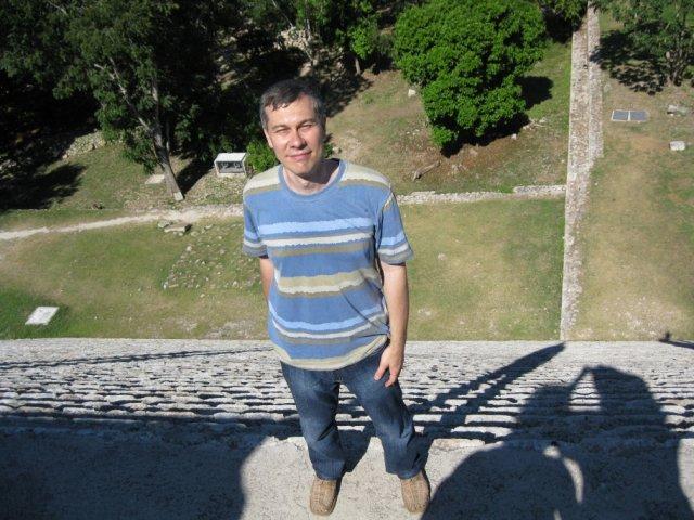 На краю крутой лестницы пирамиды в Ушмале, Мексика