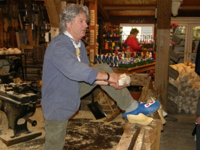 Человек изготовляющий деревянные ботинки