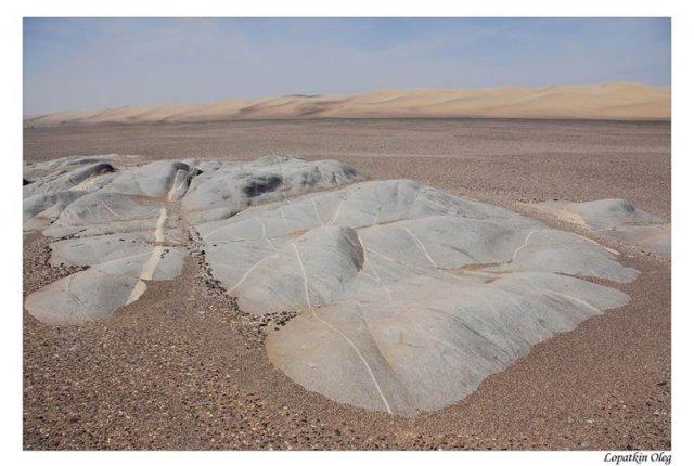 Выход скальных пород и дюны вдалеке в регионе Sceleton coast